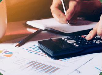 A foto mostra uma passoa fazendo anotações em um caderno enquanto utiliza uma calculadora